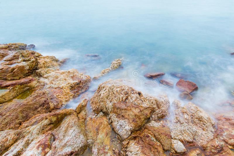Long exposure of dreamy seascape and rocky beach stock image