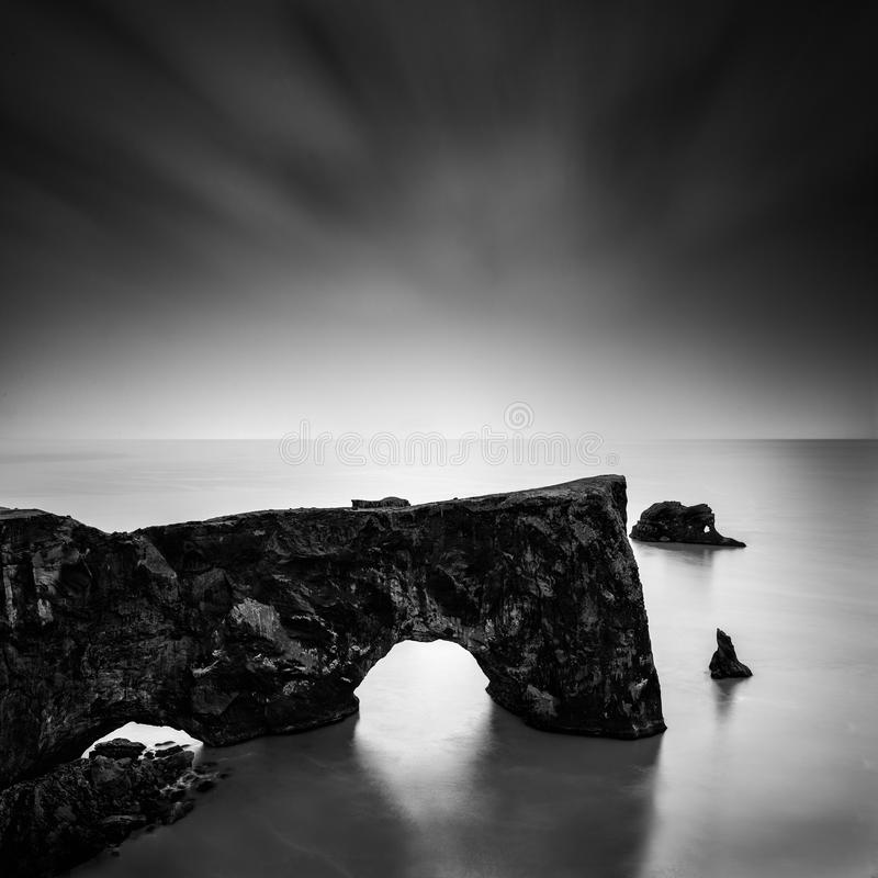Seascape with rocks in Dyrholaey, Iceland. A long exposure, fine art, black and white seascape with interesting rock formation royalty free stock photo