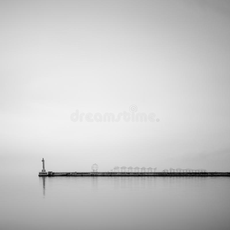 An old weatherd conctere pier in the coastal areas of Creece stock images