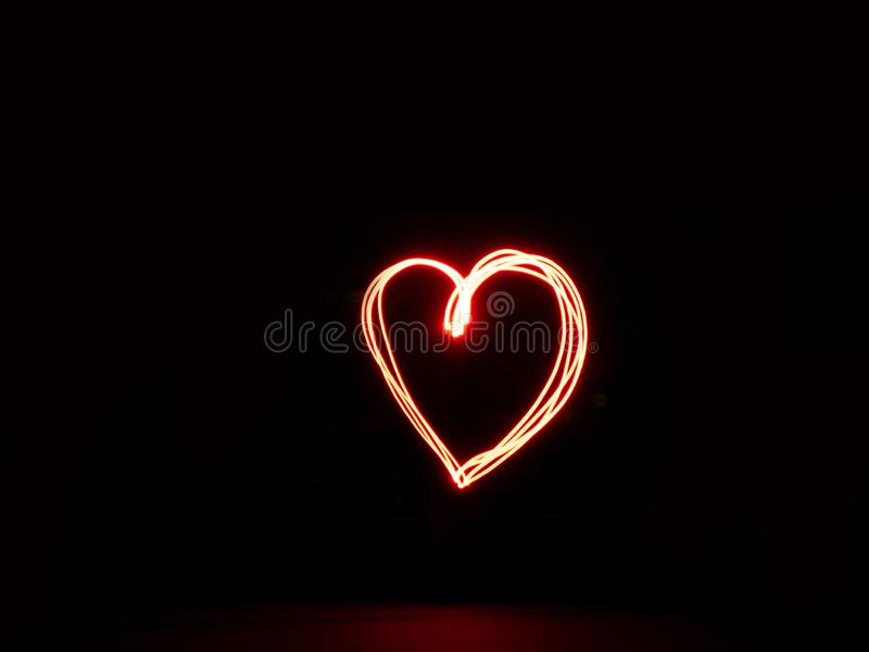 Long exposure heart red colour outline outside sign light painting with a red flashlight. Long exposure heart red colour outline outside sign light painting stock images