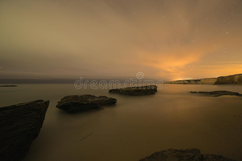 Long exposure image of coastal rocks on ocean beach. At night with blurred waves and smoothed sky and star trails royalty free stock images