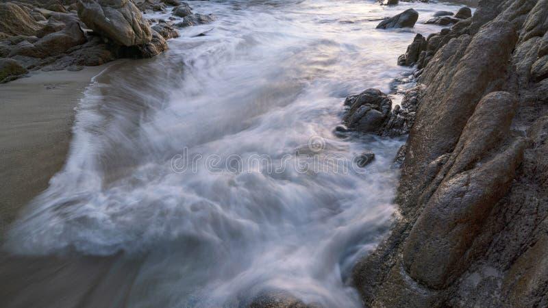 Long exposure image of crashing wave seascape with rocks royalty free stock photo