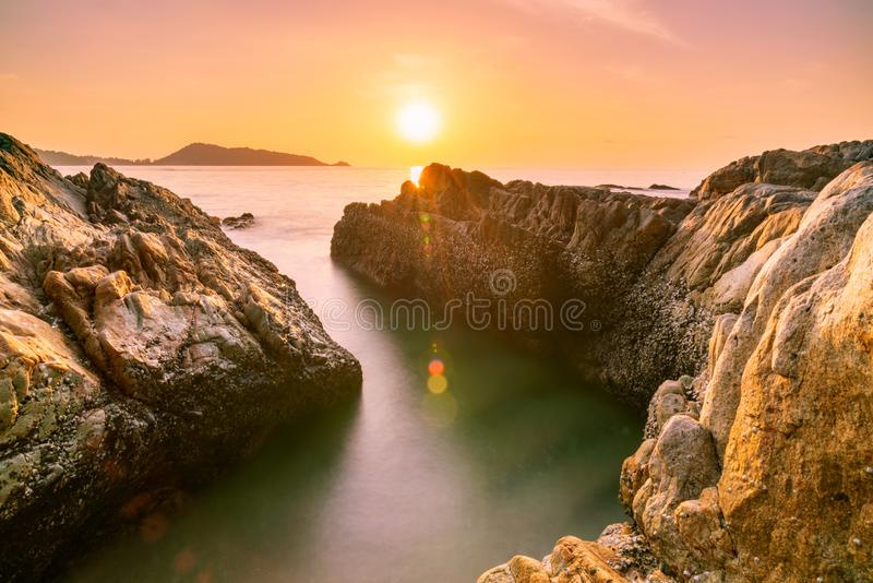 Long exposure image of Dramatic sky seascape with rock in sunset scenery background royalty free stock photography