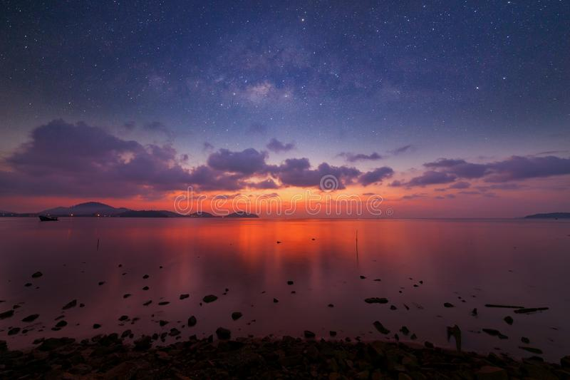Long exposure image of dramatic sunset or sunrise,sky clouds over tropical sea and milky way galaxy. Long exposure image of dramatic sunset or sunrise,sky stock photo