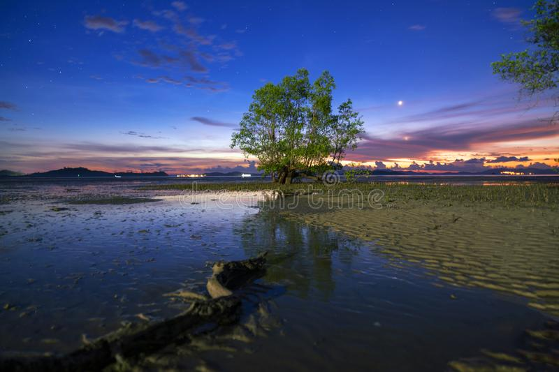 Long exposure image of dramatic sunset or sunrise,sky clouds over mountain with tree in the sea royalty free stock photography