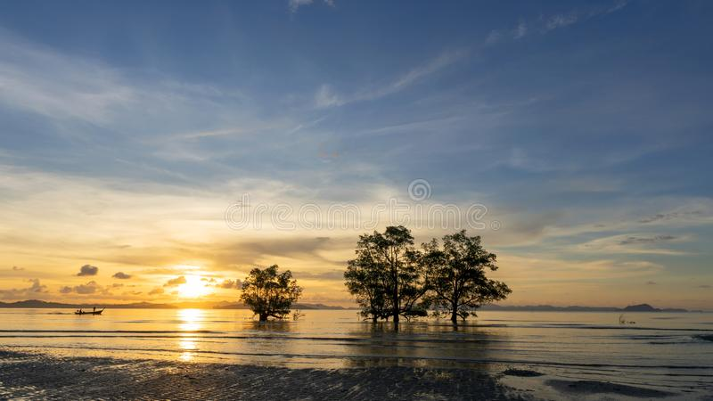 Long exposure image of dramatic sunset or sunrise sky and clouds over mountain with trees in the sea. stock photography