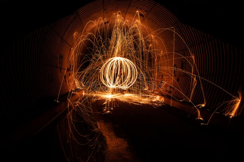 Long exposure image of orb ball of fiery sparks. In dark tunnel. Sparks cascading off sides of wall at night stock image