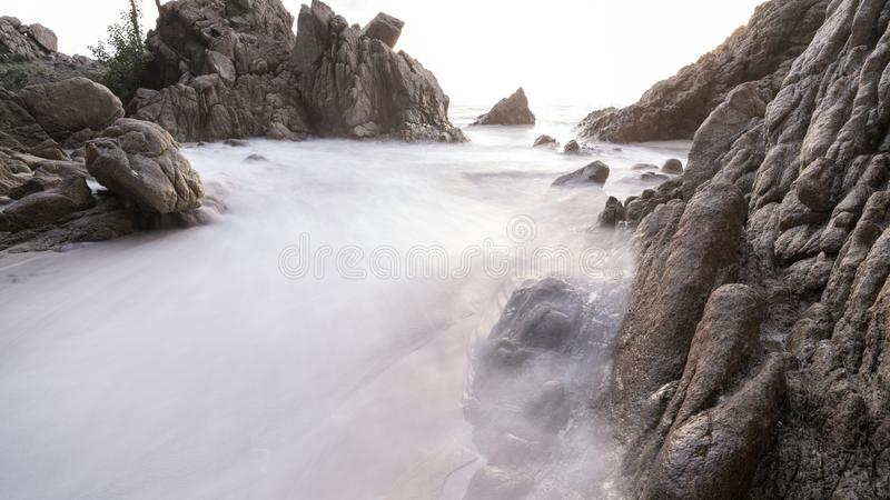 Long exposure image of  wave seascape with rock in scenery background stock photo