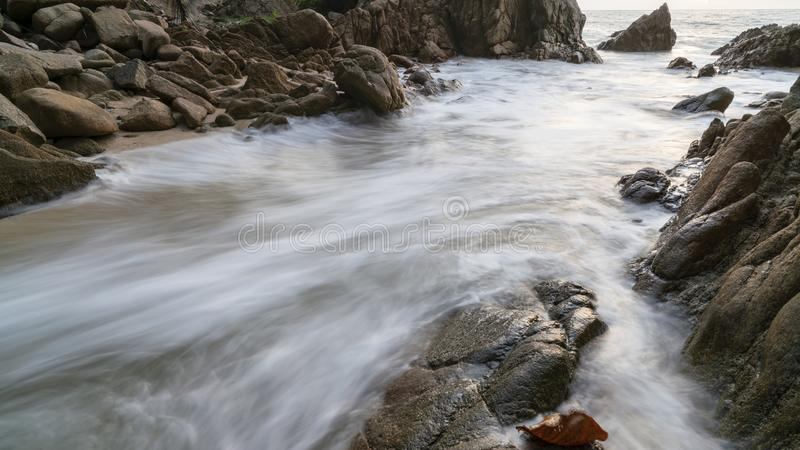 Long exposure image of  wave seascape with rock in sunset scenery background stock photos