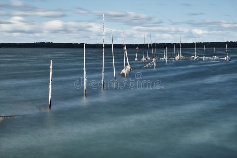 Long exposure of a lakes shore on a stormy day, creating a blurry water with poles coming out of the water holding a net royalty free stock photo