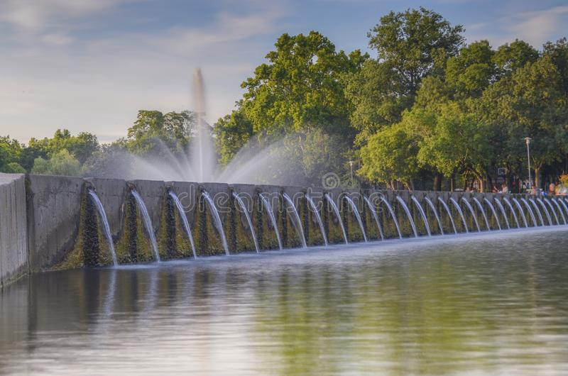 Long exposure landscape photo of water fountain in a city park tourism with sky and tree behind royalty free stock photos
