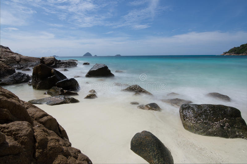 Long exposure of light waves rolling over large rocks in a idilic white sand beach in a small bay with small islands on stock photography