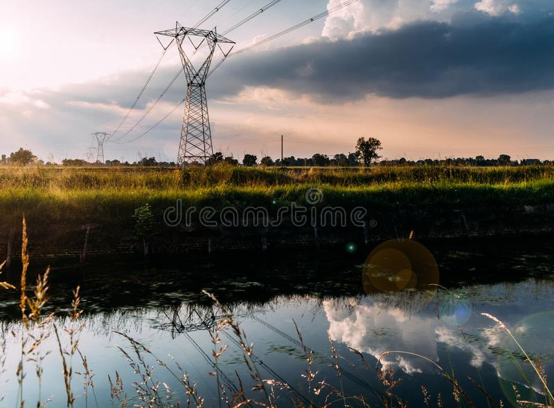 Long exposure of moving water and clouds at sunset overlooking the Naviglio Pavese, Italy. The canal links the city of Milan and P. Avia. Tall lattice towers stock photos