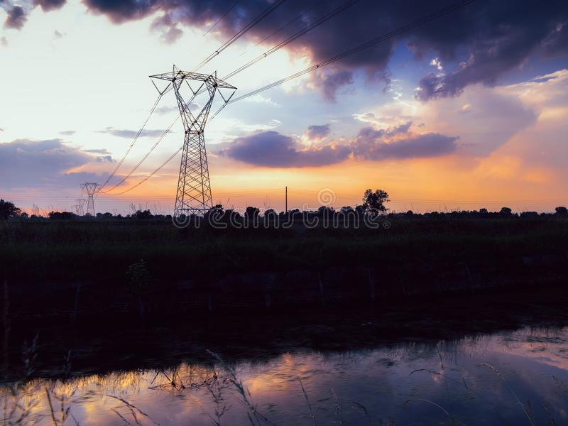 Long exposure of moving water and clouds at sunset overlooking the Naviglio Pavese, Italy. The canal links the city of Milan and P. Avia. Tall lattice towers stock images