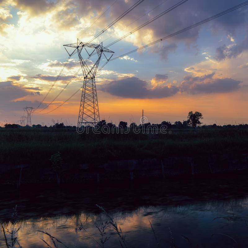 Long exposure of moving water and clouds at sunset overlooking the Naviglio Pavese, Italy. The canal links the city of Milan and P. Avia. Tall lattice towers royalty free stock photo