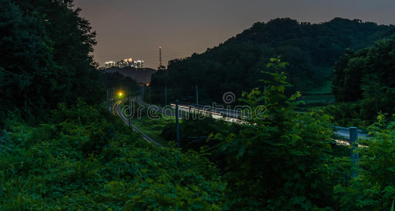Long exposure night photo of train moving at high speed. In countryside with its headlights shining and group of tall buildings on hillside in the background stock photos