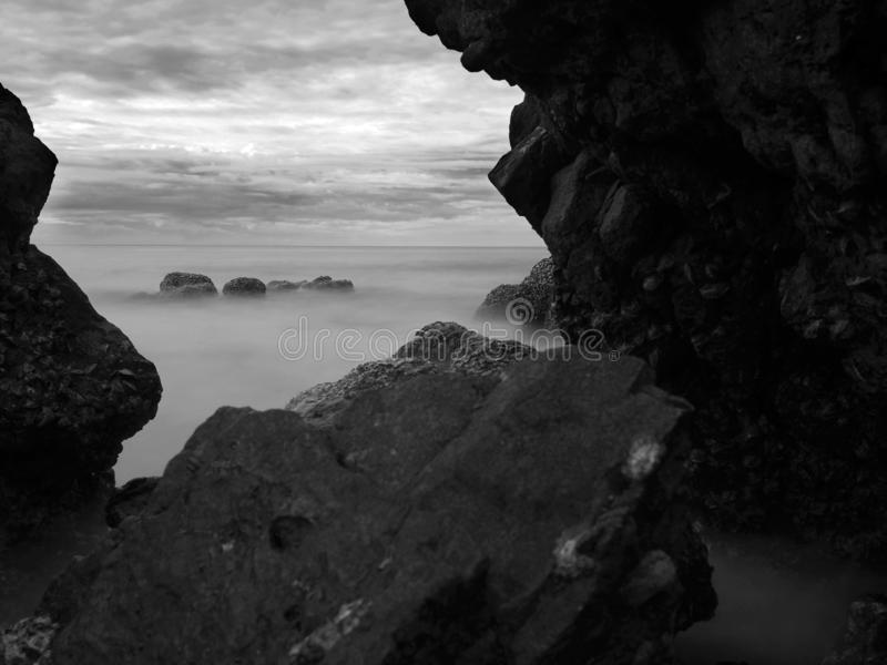Long exposure of the ocean and rock scape with cloudy sky. Black and White image stock photo