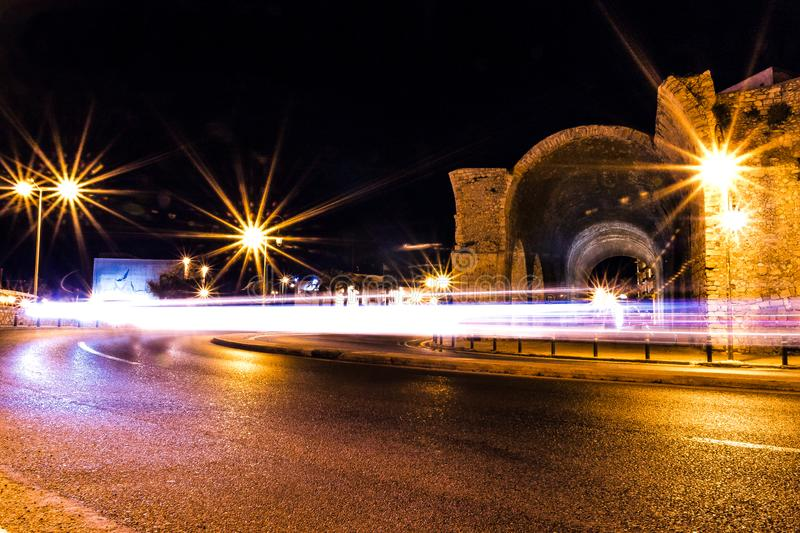 Long exposure photo car light trails on a turning road next to old heraklion city ruins low angle view royalty free stock images