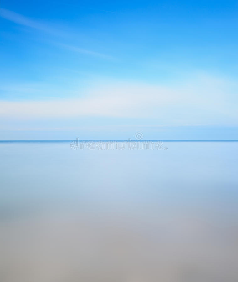 Long exposure photo. Horizon line, sea and sky. Horizon line, soft water sea and light cloudy blue sky. Long exposure photography over one minute stock image