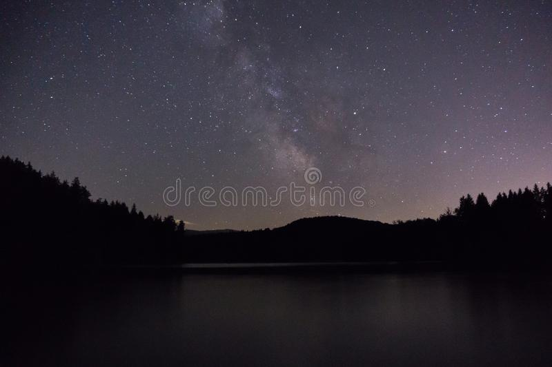Purple night sky stars over mountain lake. Milky way galaxy in summer starry night stock photo