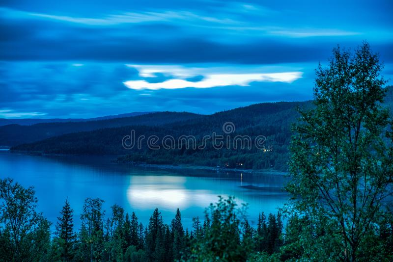 Long exposure photo 30 sec of heavy clouds over Norwegian mountains around Rossvatnet Lake, Northern Norway. Early summer night. Long exposure photo 30 sec of stock images