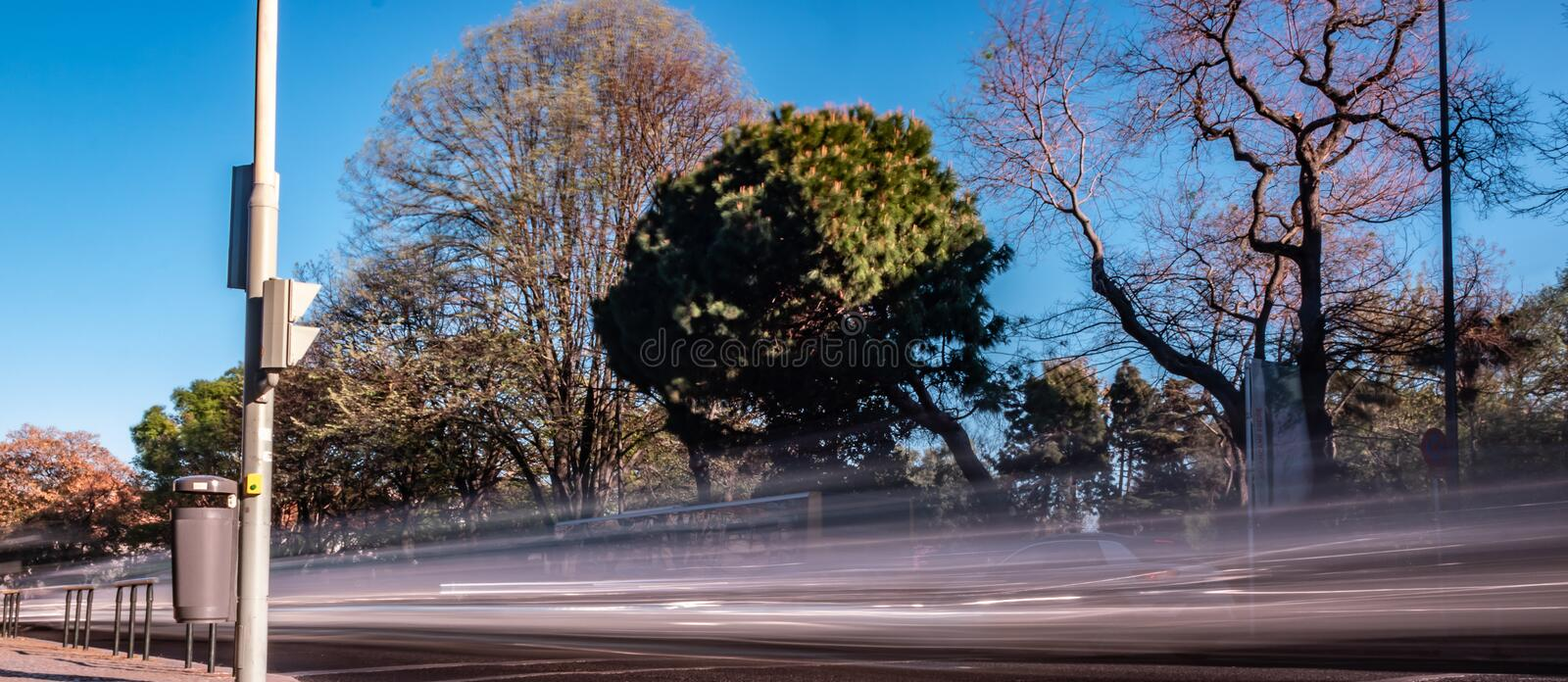 Long exposure photo taken in Lisbon alley with  Beautiful  greenery  and blue sky with  fast moving  cars leaving trail behind stock photography