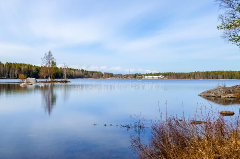 Long exposure photograph of clean water lake surrounded by pine birch trees and scenic beauty under the cloud cover blue sky and royalty free stock photos