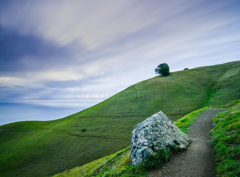 Long exposure photograph with moving clouds, a path leading off, green hills and smooth ocean. Landscape photograph of a long exposure shot on top of Mt. Tam royalty free stock photo