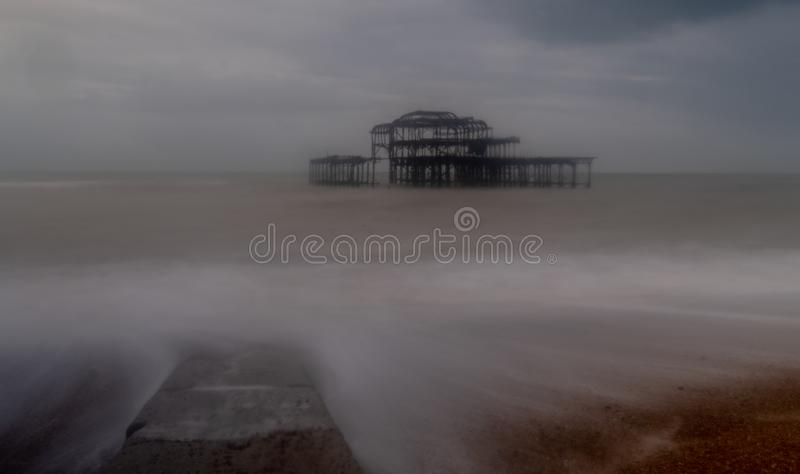 Long exposure photograph of the ruins of West Pier, Brighton Sussex UK on a cold, stormy winter`s day. Jetty in foreground royalty free stock photos