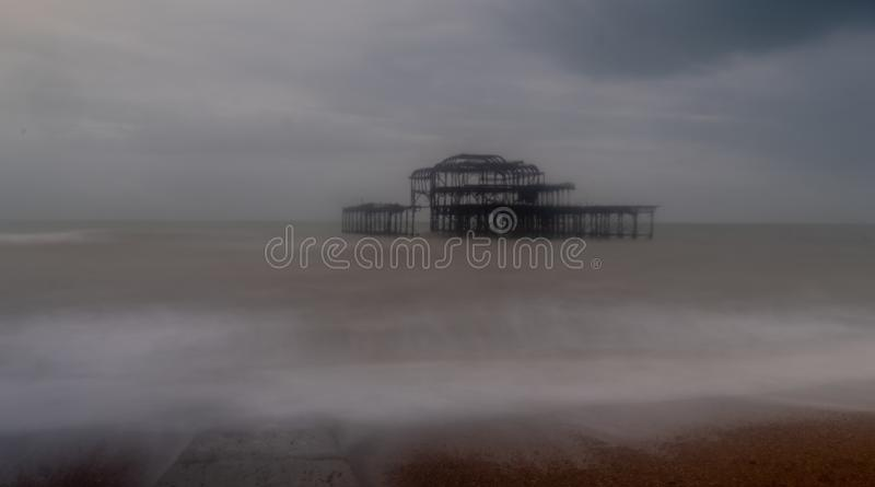 Long exposure photograph of the ruins of West Pier, Brighton Sussex UK on a cold, stormy winter`s day. Jetty in foreground stock photography