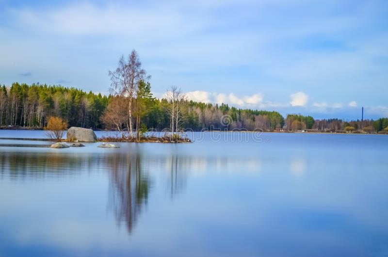 Long exposure photography of clean water lake surrounded by pine birch trees and incredible beauty under the cloud cover blue sky royalty free stock photography