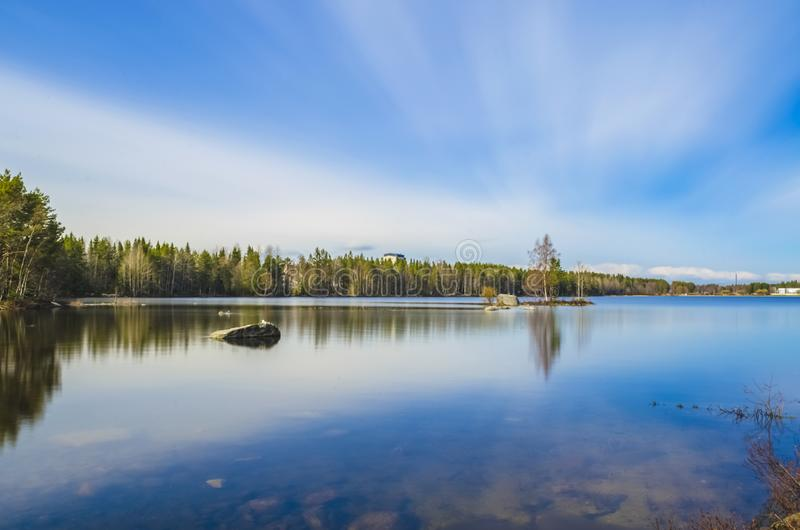 Long exposure photography of clean water lake surrounded by pine birch trees and scenic beauty under the cloud cover blue sky royalty free stock images