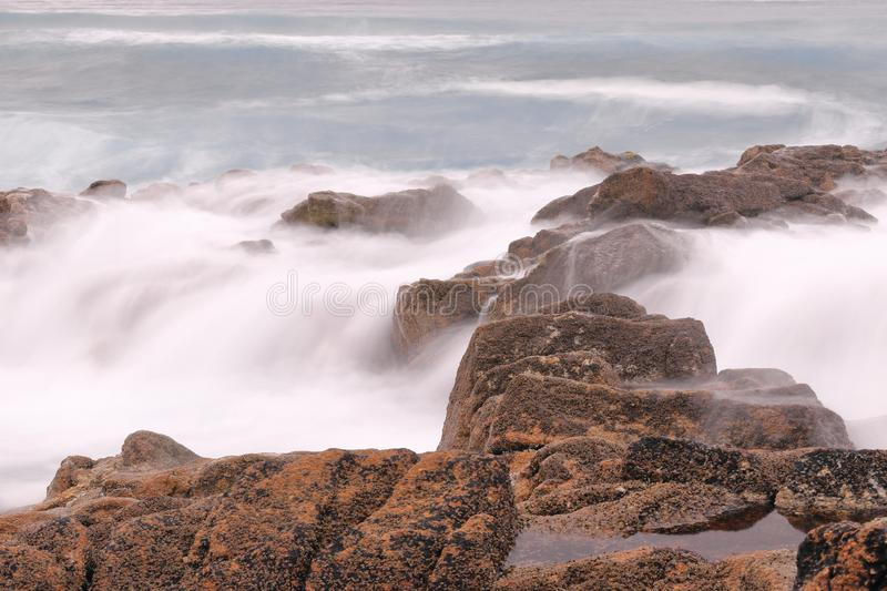 LONG EXPOSURE PHOTOGRAPHY  OF A CLIFF PEPPERED  BY THE WAVES OF THE SEA stock image