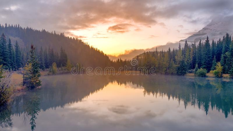 Long exposure photography of water reflection of casecade Pond during sunrise at Banff National par. K, Alberta, Canada stock image