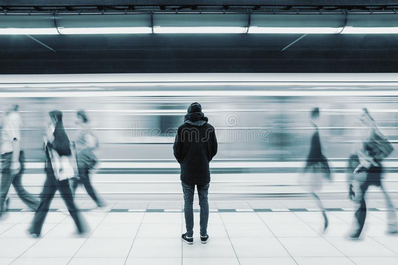 Long exposure picture with lonely man at subway station with blurry moving train and walking people. Long exposure picture with lonely young man shot from behind stock image