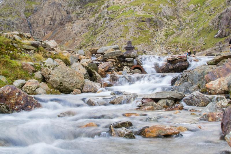 Long exposure picture of a small cold waterfalls through boulders in Snowdonia, Wales.  royalty free stock photos