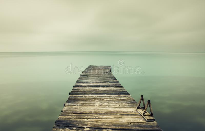 Long exposure of a pier in South Corfu Greece. Cloudy sky. Amazing Greece royalty free stock photo
