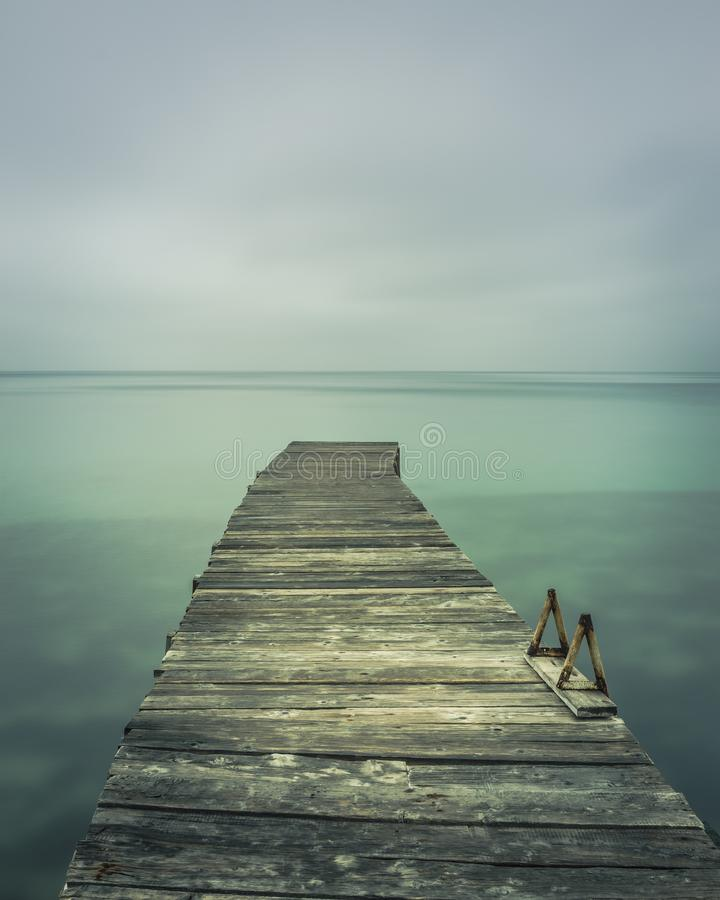 Long exposure of a pier in South Corfu Greece. Cloudy sky.Vertical. Amazing Greece royalty free stock photos