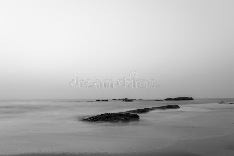 Long Exposure Of Rocky Beach In Monochrome. Long exposure of smooth water flowing through the rocks in the beach in monochrome stock image