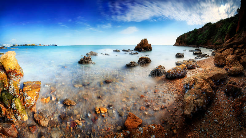 Long exposure of a rocky beach. Panorama of long exposure of a rocky beach stock photo
