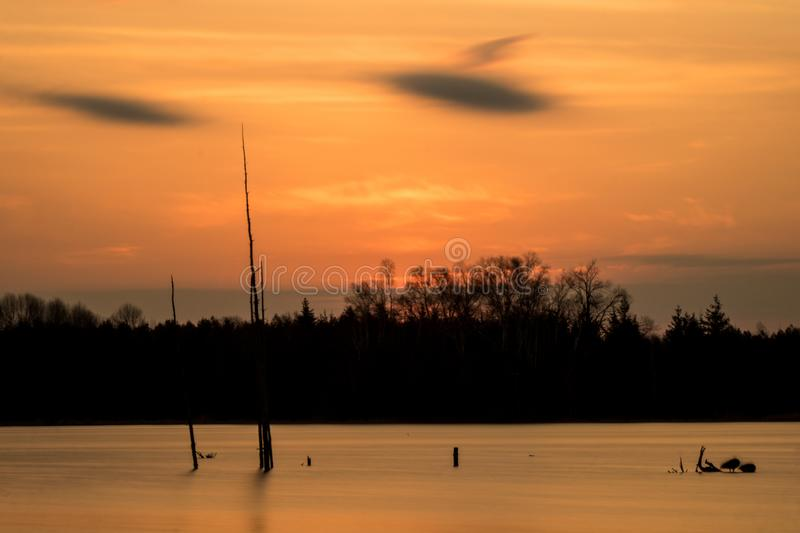 Long Exposure Scene At Island Lake Conservation Area. The sun pops over the treeline at sunrise at the eastern end of Island Lake Conservation Area in royalty free stock photography