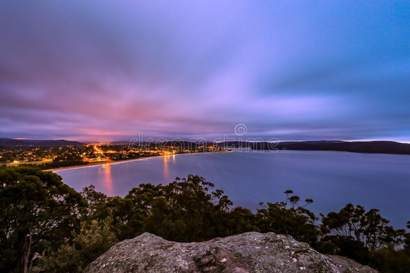 High view of ocean and city night lights against cloudy sunrise. Long exposure scene of ocean and city night lights of Ocean Beach,Umina, Australia with sunrise stock photos