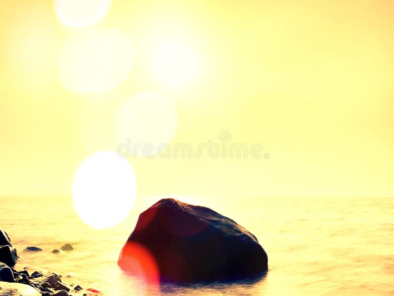 Long exposure of sea and big boulders sticking up from water within twilight time. Pink sunset. Lens defect. Long exposure of sea and big boulders sticking up royalty free stock photography