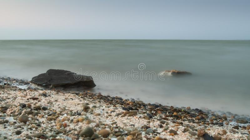 Long exposure seascape. in the foreground stones. Pink sunrise sunset stock photography