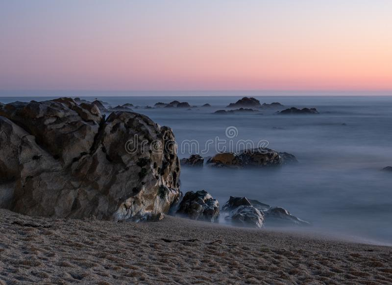 Long exposure shot on beach at dusk with milky ocean royalty free stock photos