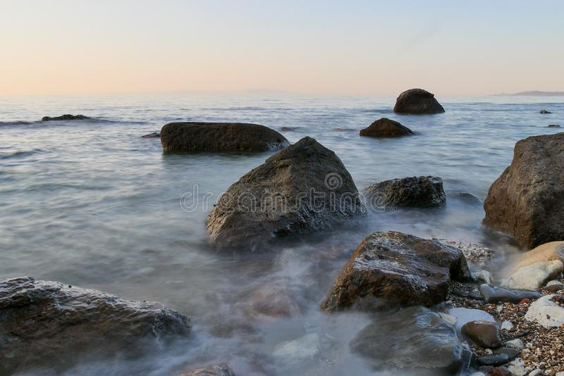 Rocks in the sea with sunset stock images