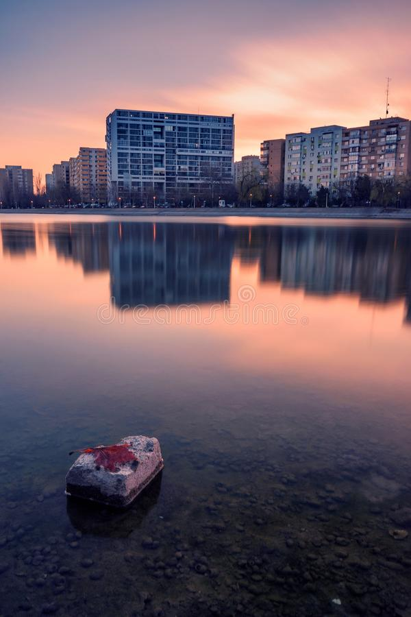 Long exposure shot in a city on the shore of a lake at sunrise with a rock in the foreground in the lake and apartment buildings stock photography