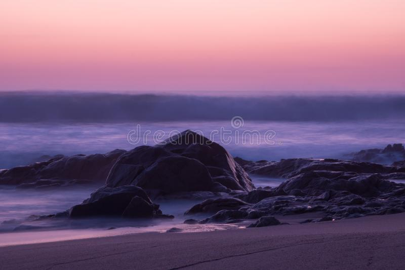 Long exposure shot at dusk over ocean with rocks in foreground. stock photography