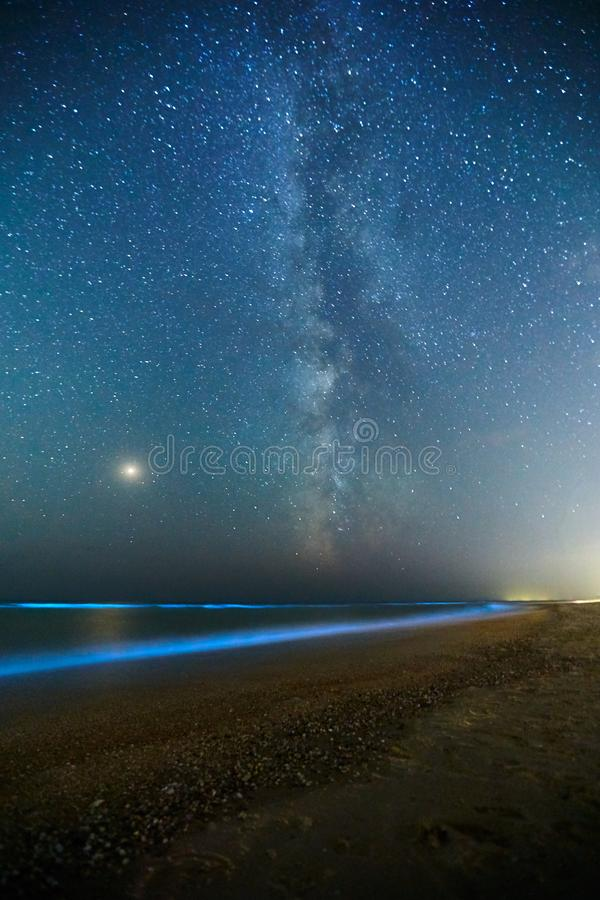 Long exposure shot of glowing plankton on sea surf and milky way. Blue bioluminescent glow of water under the starry sky. Bright Mars planet among royalty free stock images