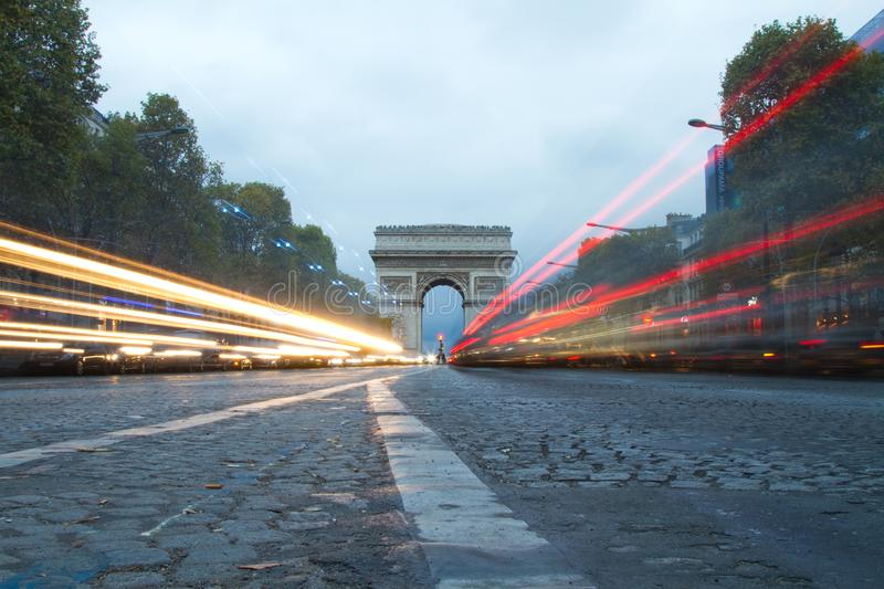 Champs Elysees and Arc de Triumph in Paris, France. A long exposure shot looking down towards the Arc de Triumph in the middle of the road of the Champs Elysees royalty free stock photo